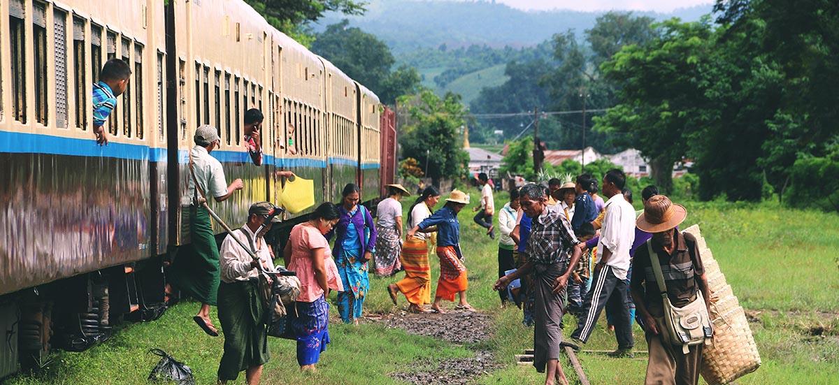 Zugfahren in Myanmar. Leute stehen vor der Bahn